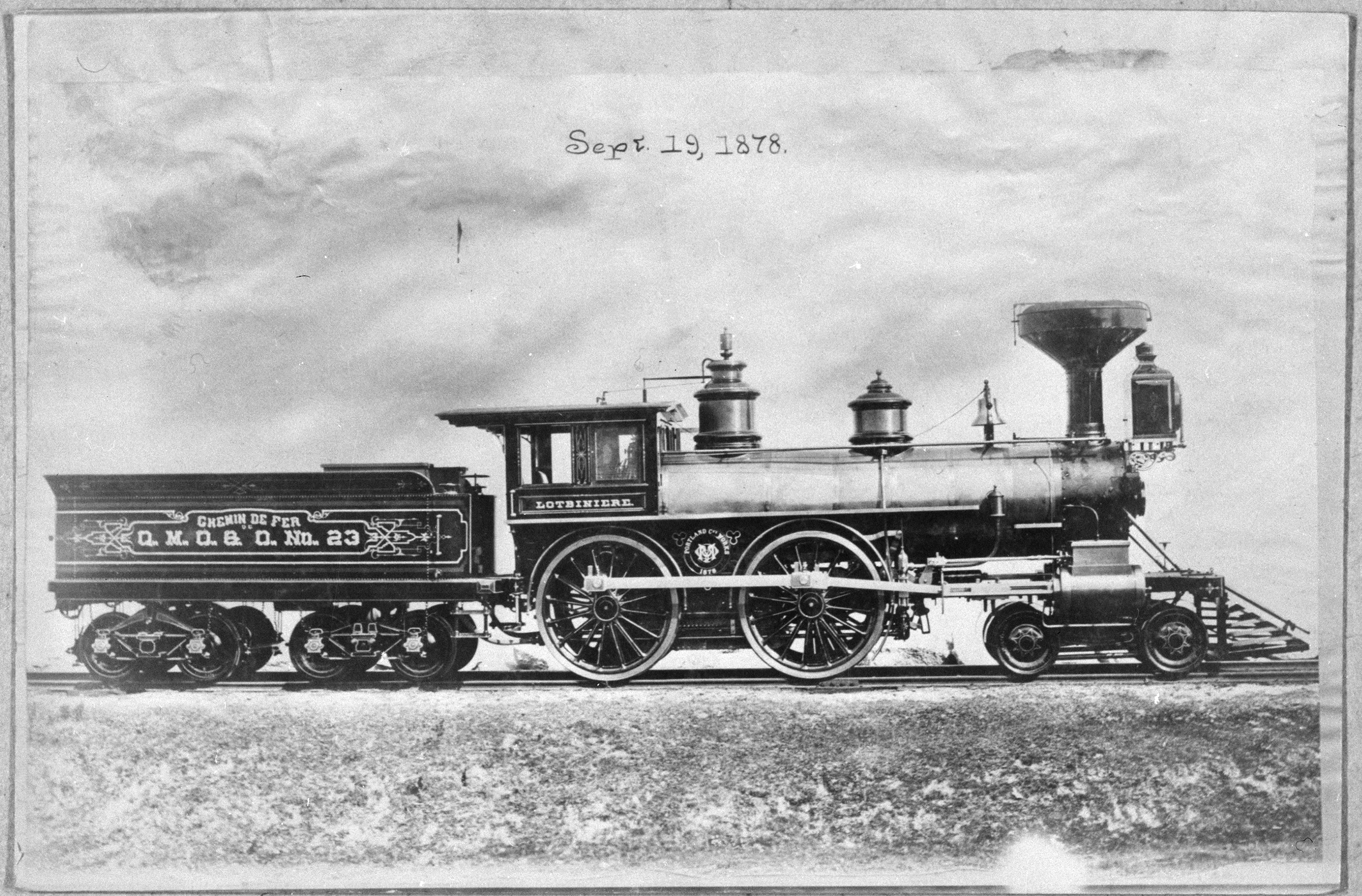 """Black & white photograph of a steam locomotive on a railway. The date """"Sept. 19, 1878"""" has been added to the photograph, above the locomotive. A small freight car is coupled to the locomotive."""