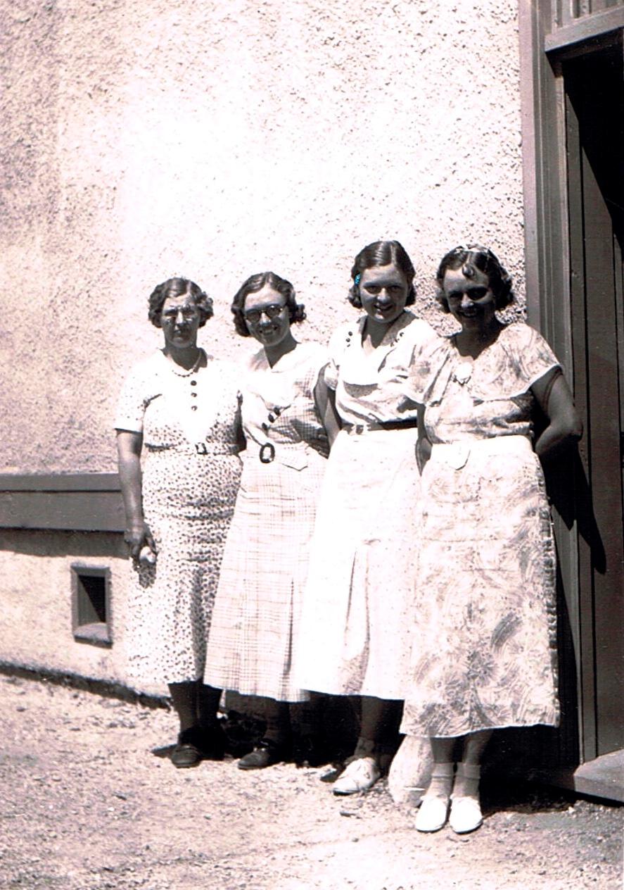 Photo en noir et blanc représentant quatre femmes, dehors, au soleil, le dos appuyé à un édifice, souriant au photographe. Elles portent toutes des robes et leurs cheveux sont coiffés à la mode des années 1930.