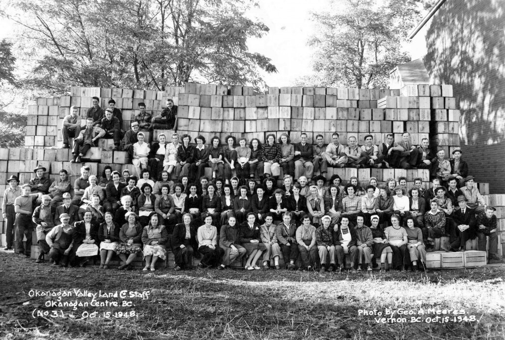 Black and white photo of a large group of men and women outside. Most are sitting on apple boxes stacked in tiers.