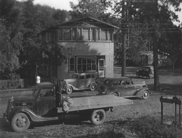 Black and white photo of a building with an older model truck and three older model cars.