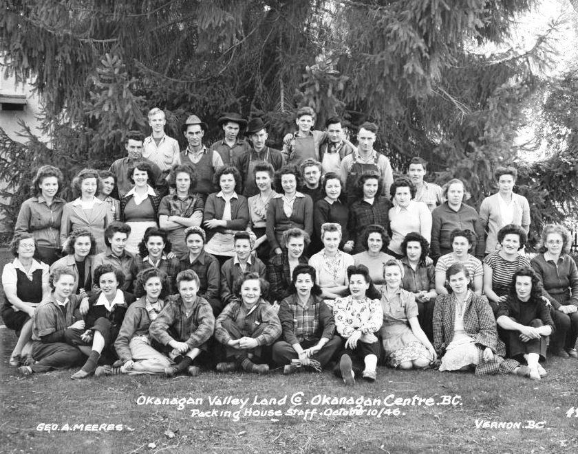 Black and white photo of 36 women and 10 men outside, arranged in four rows - two seated and two standing - with the men in the back row. A large evergreen tree is behind them.