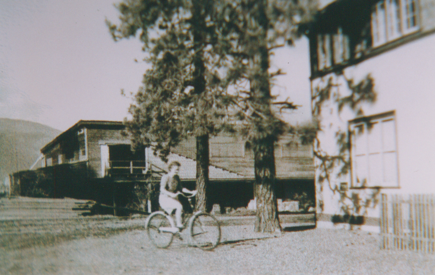 Black and white photo of a young woman riding a bicycle. A wooden building with a loading door is in the background.