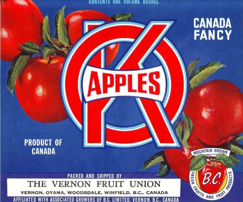 Photo en couleur d'une étiquette de caisse de pommes de la marque OK. L'étiquette comprend une inscription de couleur rouge et blanche, et cinq pommes rouges sur fond bleu.