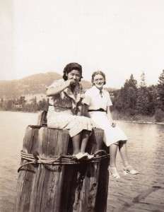 Black and white photo of two young women sitting on pilings over a lake.