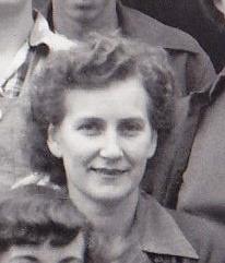 Portrait en noir et blanc d'une jeune femme souriant au photographe. Ses cheveux bouclés sont coiffés en arrière.
