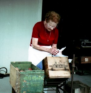 Colour photo of a senior woman standing on a patio, wrapping a wooden apple and putting it into one of two apple boxes in front of her. She has curly red hair and wears a red sweater.