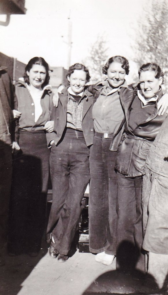 Black and white photo of four women standing outside. They are wearing pants and have their arms across each other's shoulders.
