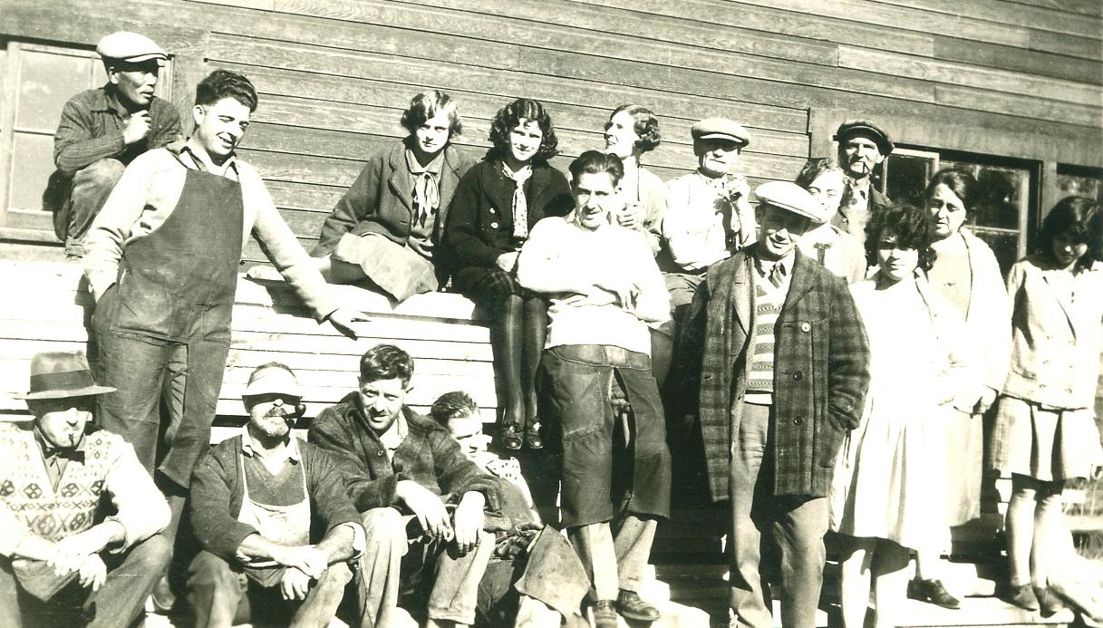 Photo spontanée en noir et blanc représentant dix hommes entre 20 et 45 ans et sept jeunes femmes portant tous des tenues décontractées, devant un édifice en bois. Certains d'entre eux sont assis sur des piles de bois, d'autres se tiennent debout ou penchés vers l'arrière. Deux hommes fument la pipe.