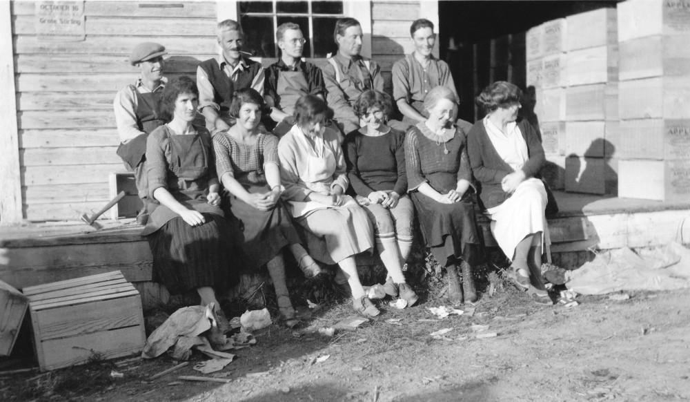 Photo en noir et blanc représentant six femmes (au premier plan) et cinq hommes (à l'arrière-plan) assis devant un vieil édifice. Ils portent des vêtements des années 1920.