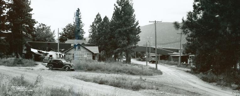 Photo en noir et blanc d'une vieille voiture devant une maison de bois.