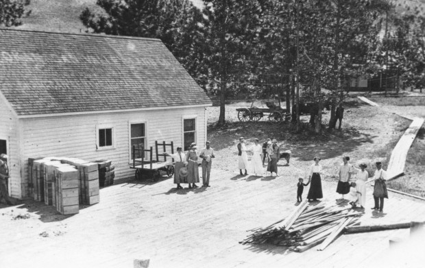Black and white photo of several men, women, and children standing on a large wooden patio in front of a white wooden building, all wearing early 1900's style clothing. To the left are stacked apple boxes and a cart. In the background are trees, grass, a narrow wooden sidewalk, and a horse and buggy.