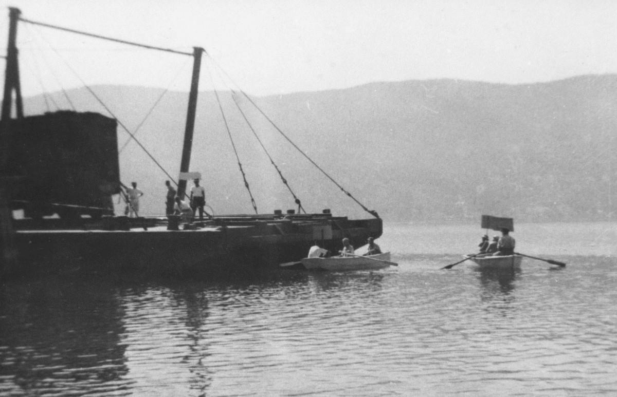 Photo en noir et blanc représentant une barge sur laquelle quatre hommes se tiennent debout. Trois personnes sont assises dans chacun des deux canots à rames qui se trouvent près de la barge. Trois personnes arborent des panneaux.