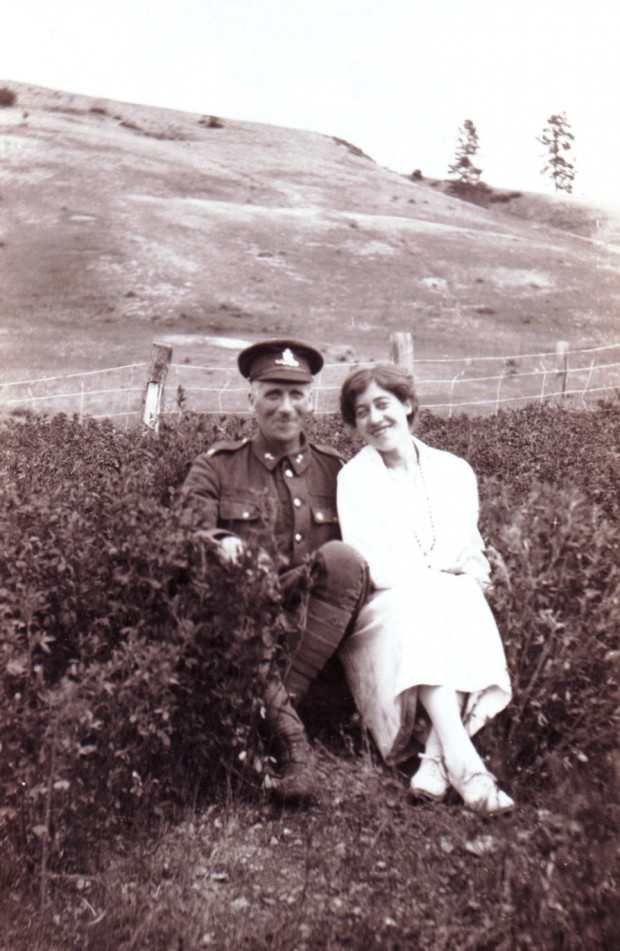 Black and white photo of a man in army uniform and a smiling woman seated outside in a field, with hills in the background.