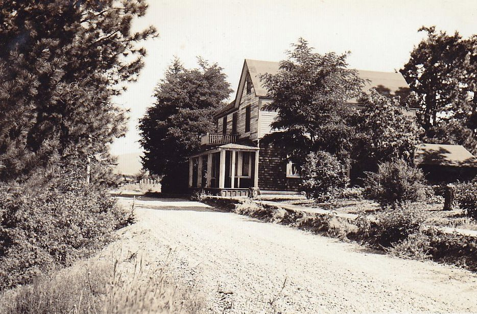 Black and white photo of a wooden house on an unpaved road.