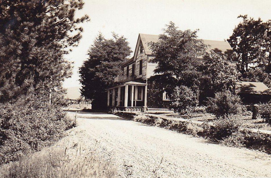 Photo en noir et blanc d'une maison en bois près d'un chemin de terre.