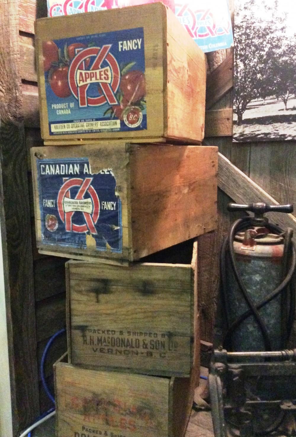 Photo en couleur représentant une pile de caisses de pommes en bois. Les deux caisses du haut portent des étiquettes de la marque OK.