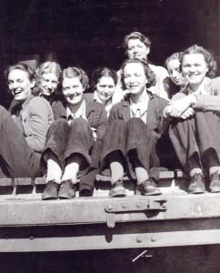 Photo en noir et blanc représentant huit femmes assises à l'entrée d'une rampe de chargement.