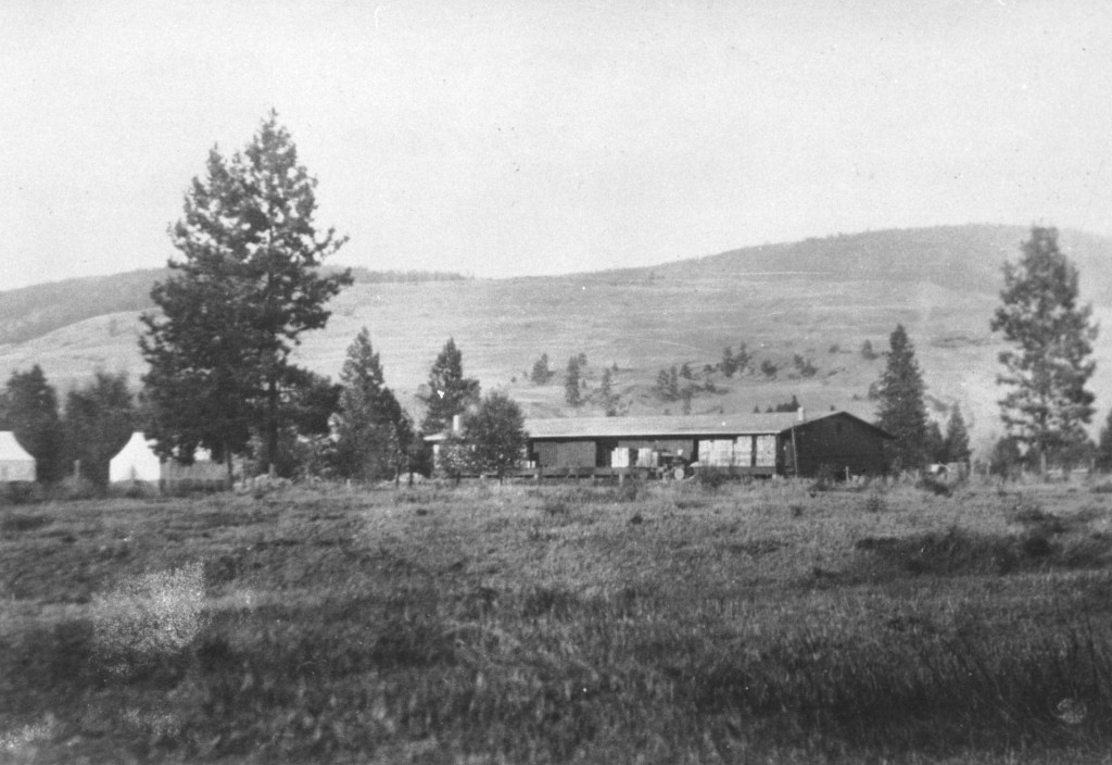 Black and white photo of an old one-story building in a field with hills behind.