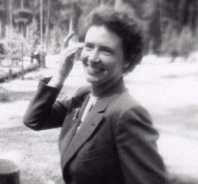 Portrait spontané en noir et blanc d'une femme souriante en train de marcher.