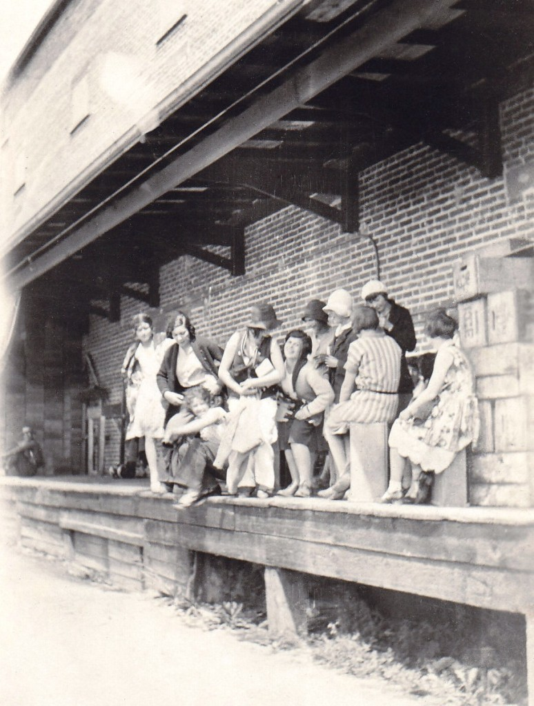 Black and white candid photo of ten women standing or sitting on a deck in front of a brick building.