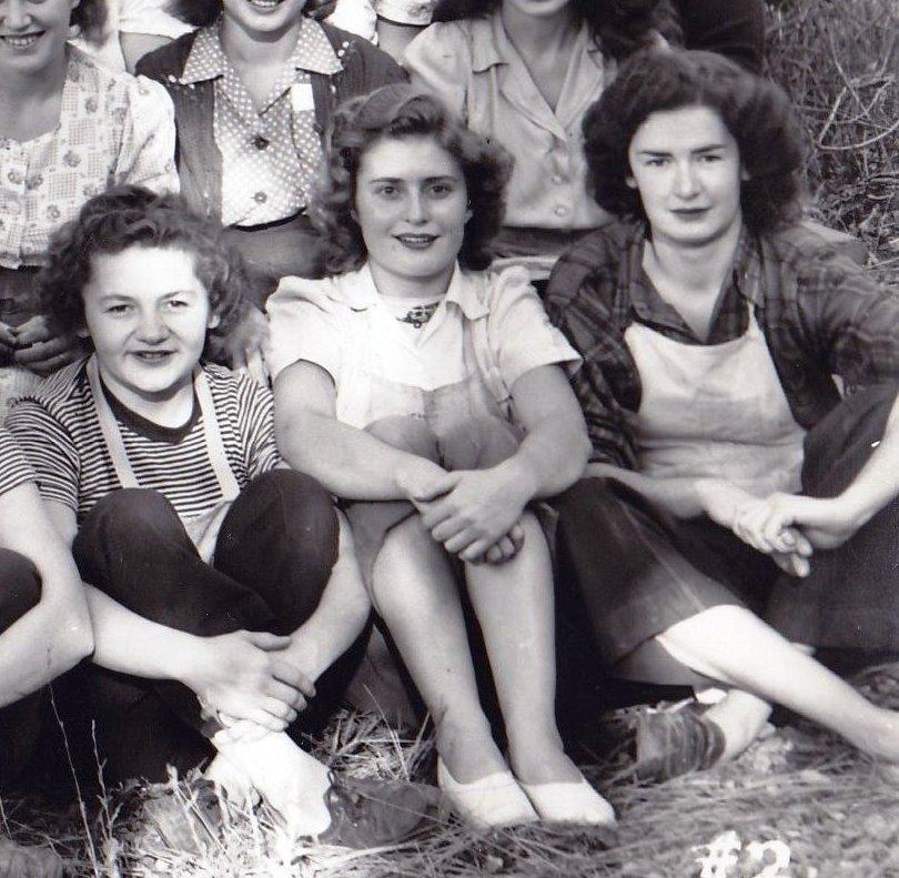 Segment d'une photo en noir et blanc représentant trois jeunes femmes assises dans l'herbe.