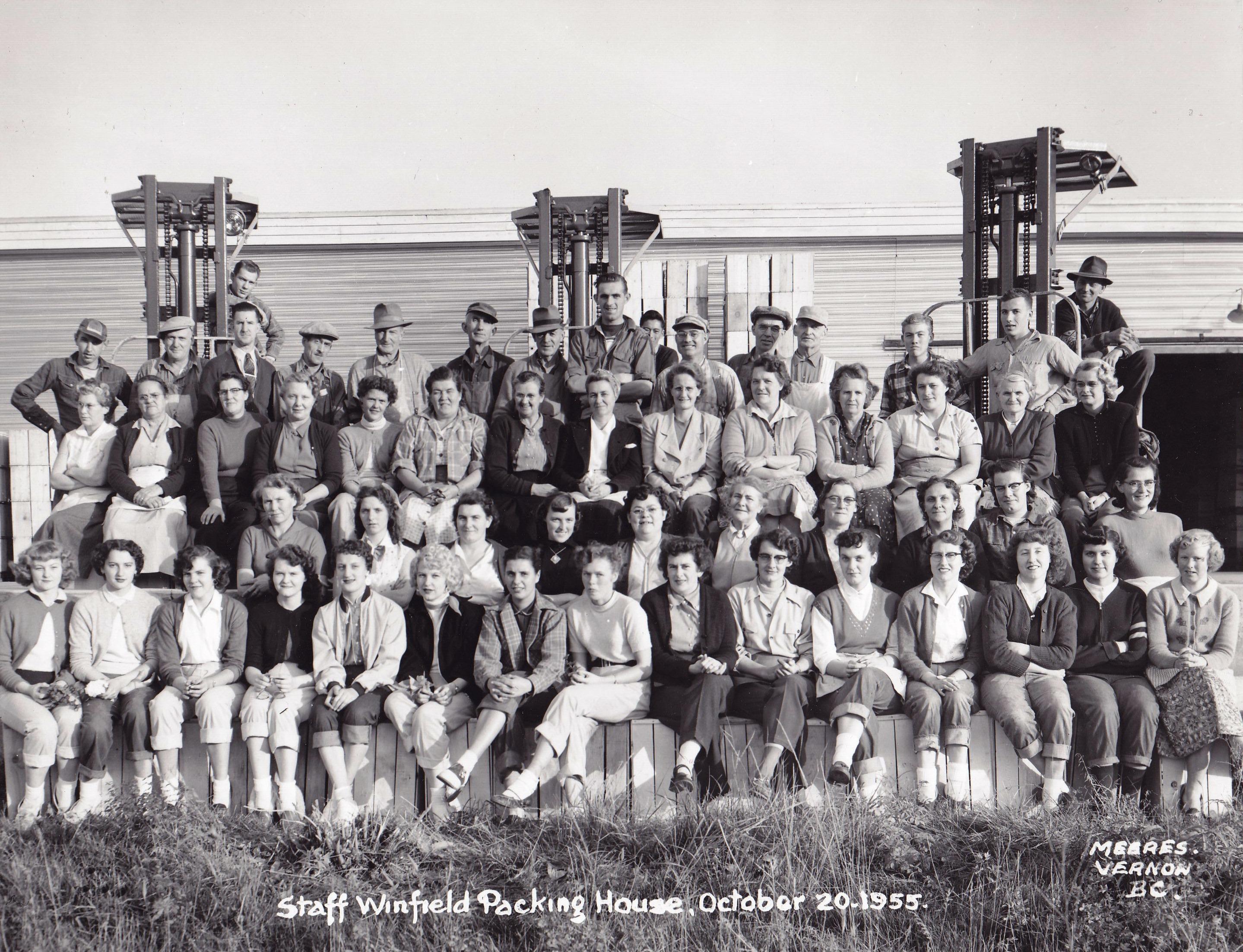 Photo extérieure en noir et blanc représentant un grand groupe de femmes et d'hommes disposé en gradins. Trois grands élévateurs à fourche et un édifice se dressent à l'arrière-plan.