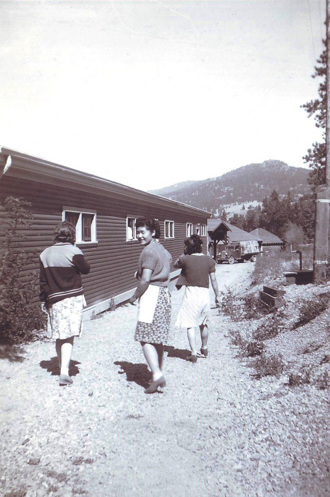 Black and white photo of three women walking along a path next to a one-story wooden building. Two women are facing forward, away from the photographer and the third is looking back over her shoulder.