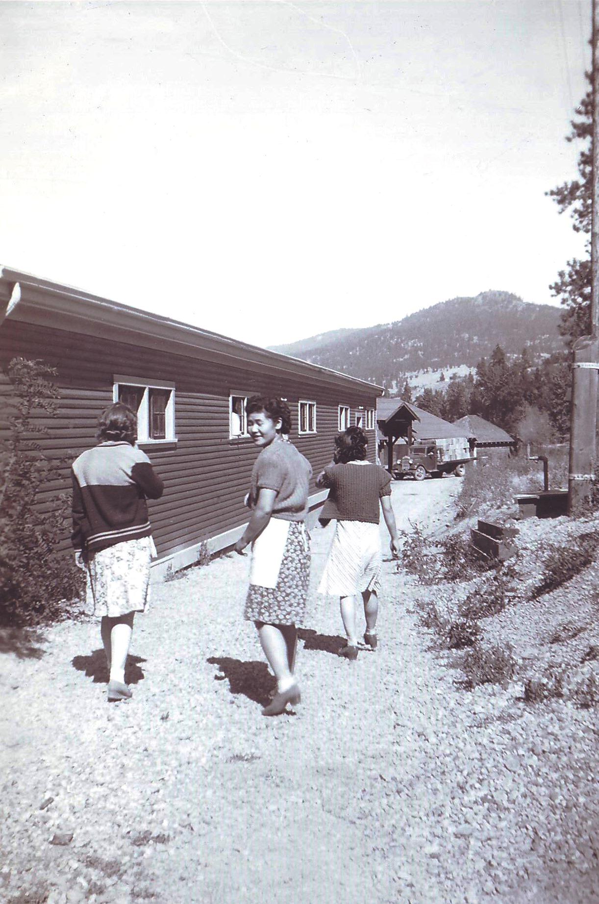 Photo en noir et blanc représentant trois femmes marchant le long d'un sentier près d'un édifice de bois d'un étage. Deux des femmes tournent le dos au photographe et la troisième se retourne pour le regarder.
