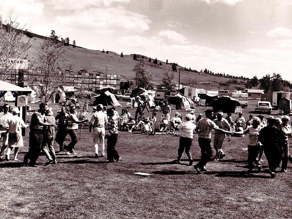 Photo en noir et blanc représentant un grand groupe d'hommes et de femmes dansant dans un champ alors que d'autres sont assis et les regardent. Derrière les danseurs, on aperçoit deux vieilles voitures, des caravanes, des tentes et des piles de caisses de pommes.