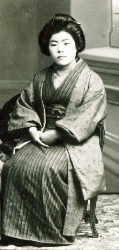 Photo en noir et blanc d'une jeune femme assise. Elle porte un costume d'apparat japonais traditionnel.