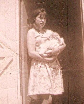 Jane Hayse avec un petit bébé. Cette photo montre Jane Hayse juste avant qu'elle quitte Parker's Cove pour aller travailler à St. John's.