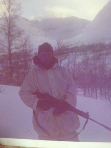 Al Murphy, wearing a white parka, stands in the snow holding his rifle while on military exercises in Norway in the late 60s