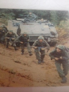 Al Murphy and other soldiers on training exercises. Soldiers with weapons move in formation in front of an army tank.