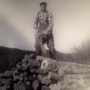 Wilson King stands on top of a pile of logs with a chain saw in hand.
