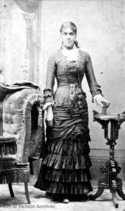 black and white photo, young adult female standing next to a chair posing for the camera with a slight smile; wearing a long formal dress, with a white under-blouse, ruffled at the neck and cuffs, long hair in a ponytail
