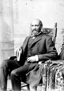 black and white professional studio portrait of middle-aged man, seated, dark hair and trimmed dark beard, wearing formal suit