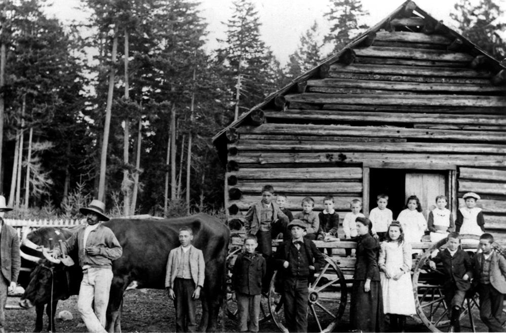 Bâtiment à un étage en bois rond. Au premier plan, un cheval et un chariot; les conducteurs et les enfants s'y tiennent devant