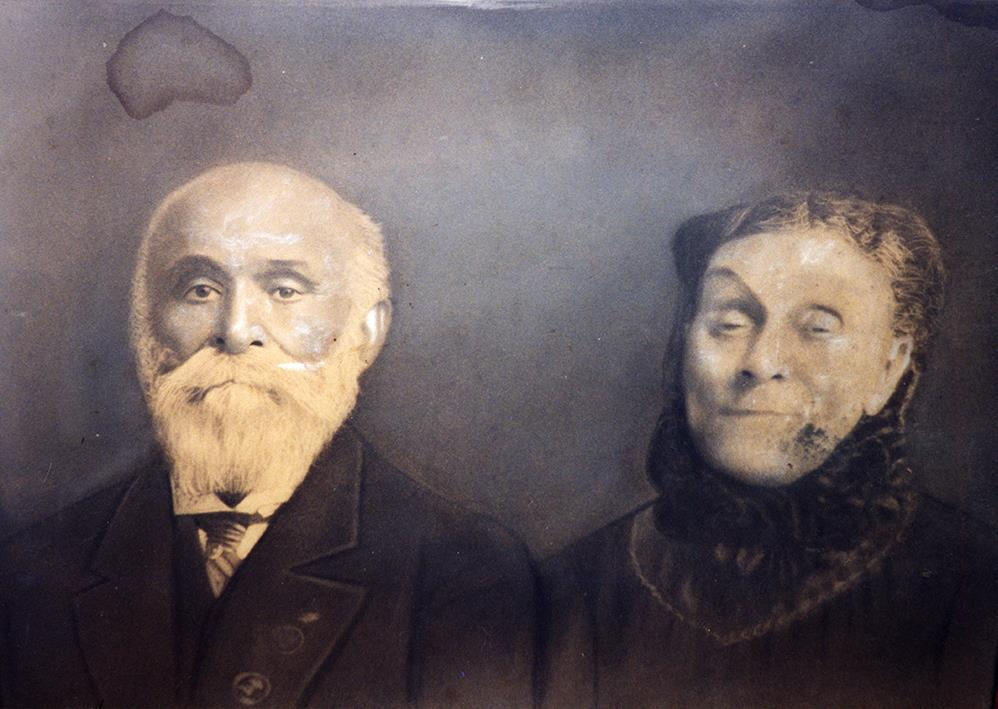 Sepia colored portrait of senior couple, formal dress,seated, male; left full white beard, female right hair pulled back, dress with high trimmed collar.