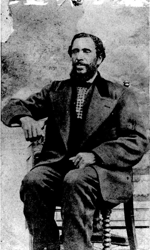 portrait studio professionnel en noir et blanc d'un homme d'âge moyen, assis, cheveux foncés et barbe taillée, portant un costume formel