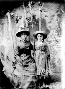 black and white professional portrait 2 sisters in colonial dresses wearing hats, girl age 23 left is seated, girl age 11 is standing, deciduous saplings in background