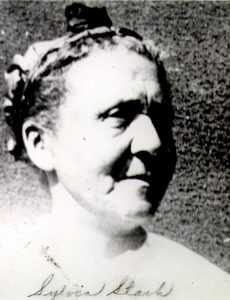 black and white portrait of middle-aged woman hair pulled back with a decorative band.