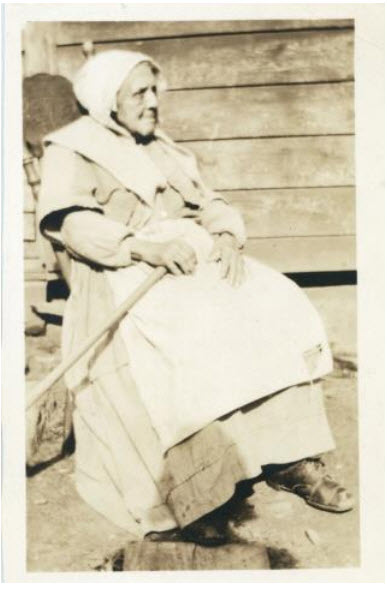 sepia photo, old woman wearing bonnet, long work dress, apron sitting in rocking chair on porch holding rake across lap in left hand.