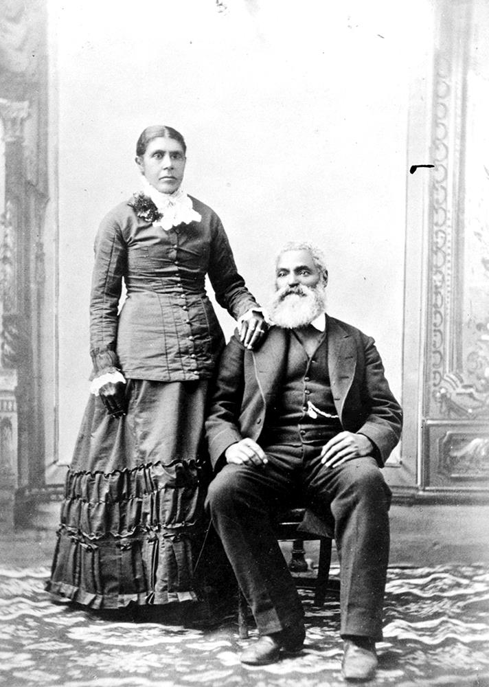 Black and white professional studio portrait woman standing, man seated. Nancy's hair parted in the centre, pulled back into a bun. Her right hand rests on Charles shoulder. Charles, seated to her right, with his right foot slightly forward wearing a dark suit and vest, his watch chain is visible from his vest pocket. Charles hair is white; he has a moustache and full beard.