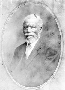 black and white professional studio portrait in oval frame, senior man with white hair and beard and moustache in formal suit and tie.
