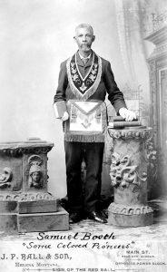 man with gray beard standing, dressed in masonic regalia.