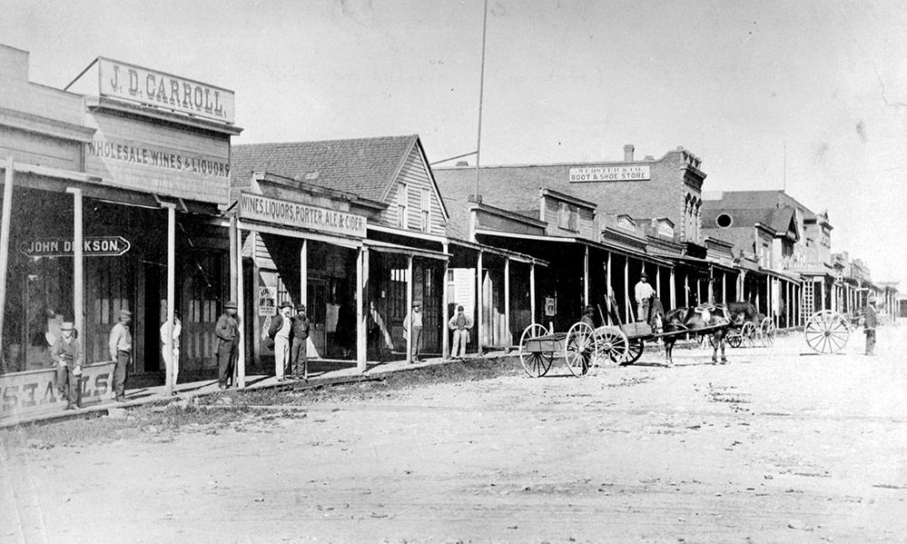 wide dirt street lined on both sides with businesses, constructed of wood and brick of various lengths and heights and roof types. People are walking or standing at storefronts, horses and carts travel the streets.