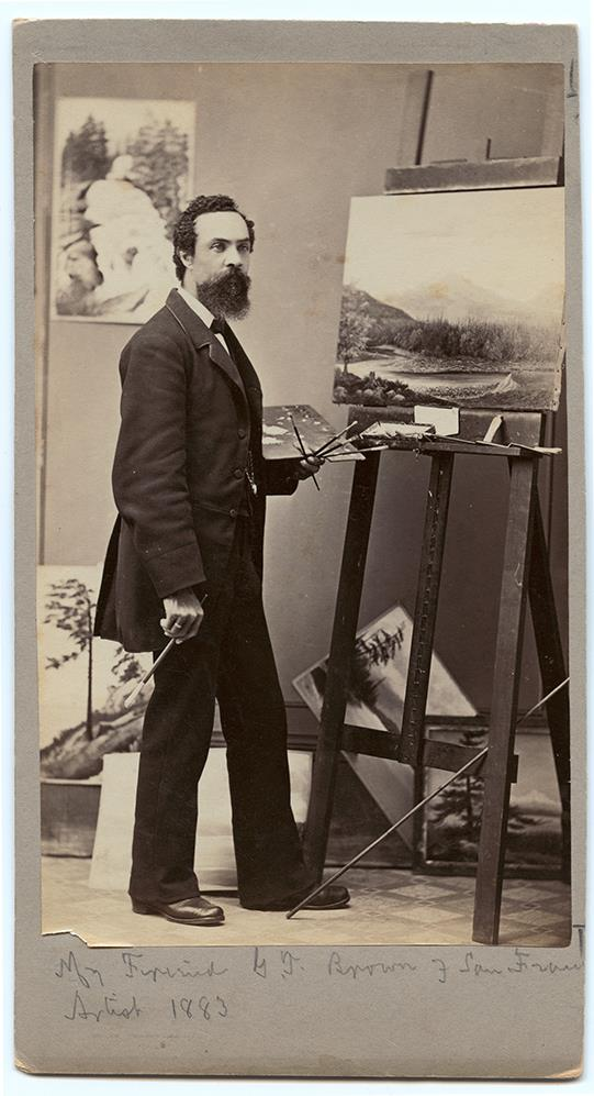 young bearded man standing at easel with paint brushes and palette in left hand and 1 brush in right hand