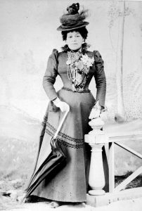 black and white professional studio photo of woman standing regally, leaning on closed umbrella; wearing tiered Victoria hat adorned with lace and flowers, long flared dark dress, ruffles and piping adorn the neck and bodice