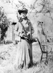 black and white professional photo of woman standing regally in a garden, wearing tiered Victoria hat adorned with lace and flowers, long flared light-colored dress, with hip-length suit jacket with ruffled lapel.