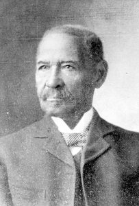 Portrait. Black male age 50, dressed semi-formally wearing jacket, vest, winged-collar white shirt with a striped pattern bow-tie.